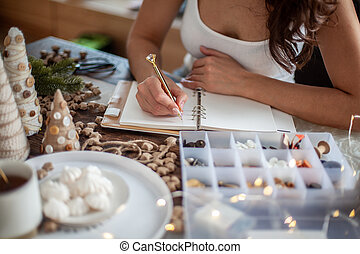 Top view of young woman is writing goals for New Year 2021 on diary on desk with Christmas Tree