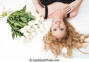 Top view of young woman lying on floor with flowers