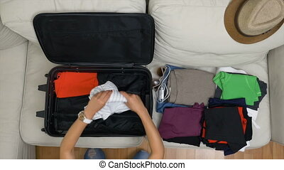 Top view of young woman organizing clothes into suitcase