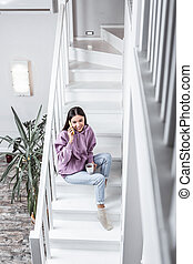 Top view of young woman sitting on stairs in light spacious house