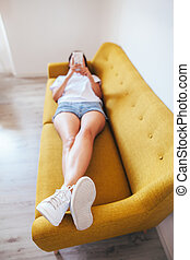 Top view of young woman using smartphone while lying in bed