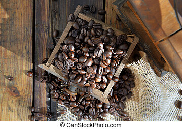 top view on a drawer of a coffee grinder filled with grain on rustic wooden background