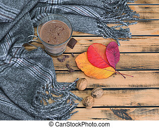 top view on a mug of hot chocolate with scarf and red leaf on a wooden table