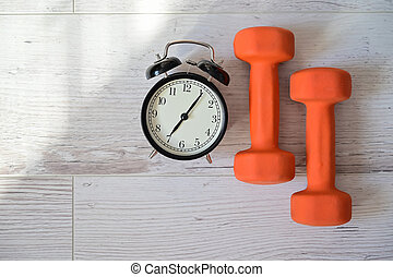 Top view on a pair of orange dumbbell and alarm clock. The concept of doing sports early in the morning. Time for self-training at home.