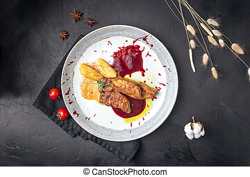 Top view on a plate with fois gras. Dark grey background