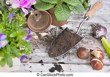 top view on a shovel full of soil and flower pots on a table