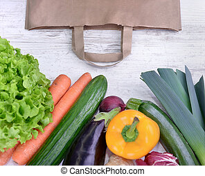 top view on a various colorful vegetables and a paper bag on a white table