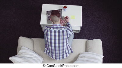 Top view on a young student man with laptop working or studying at home. Freelancer male writing down interesting facts in to his notebook. Student concept. Freelancer concept. Prores 422.