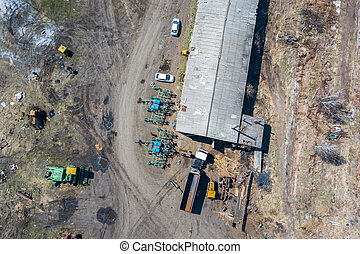 Top view on agricultural machinery near the hangar in the village for planting and harvesting. Tractor and truck in green and blue. Agriculture and farming.