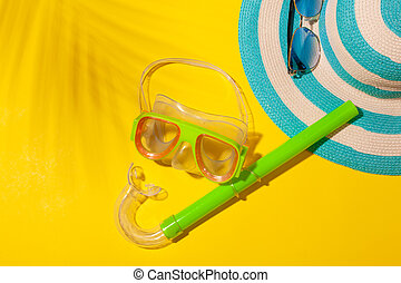 Top view on beach accessories on yellow background - striped blue hat and diving mask. Concept of beach holiday, sea tour, warm sunny summer. Advertising space