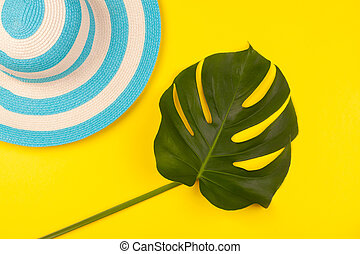 Top view on beach accessories on yellow background - striped blue hat and monstera leaf. Concept of the long-awaited vacation at sea and travel. Advertising space