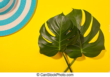 Top view on beach accessories on yellow background - striped blue hat and monstera leaves. Concept of the long-awaited vacation at sea and travel. Advertising space