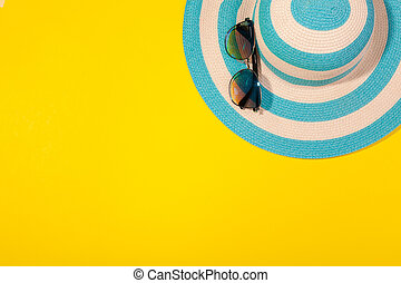 Top view on beach accessories on yellow background - sunglasses and striped blue hat. Concept of beach holiday, sea tour, warm sunny summer. Advertising space