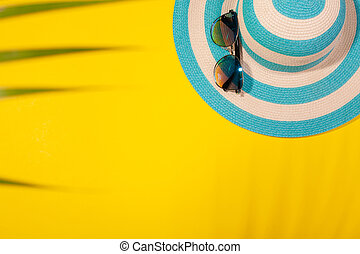 Top view on beach accessories on yellow background - sunglasses and striped blue hat in palm leaf shadow. Concept of beach holiday, sea tour, warm sunny summer. Advertising space
