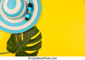 Top view on beach accessories on yellow background - sunglasses, striped blue hat and monstera leaf. Concept of the long-awaited vacation at sea and travel. Advertising space