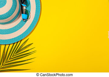 Top view on beach accessories on yellow background - sunglasses, striped blue hat and palm leaf. Concept of beach holiday, sea tour, warm sunny summer. Advertising space