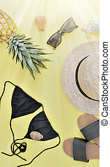 top view on beach accessories with pineapple on yellow background and sunlight effect