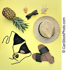top view on beach accessories with pineapple on yellow background- summer vacation concept