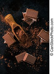 Top view on cocoa in spoon and few pieces of chocolate