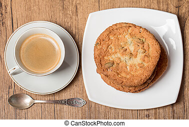 Top view on cup of coffee and plate with cookies