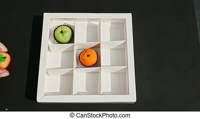 top view on female hand puts fruits shaped marzipan candy into white gift box