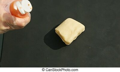 top view on female hands in confectionery gloves pour orange colorant on small cube of white homemade marzipan mass on black table surface