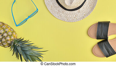 top view on female sandale straw hat, sunglasses and pineapple on yellow background