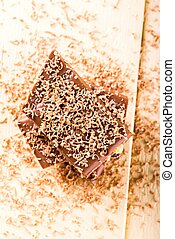 Top view on few pieces of chocolate in a stack with grated shavings