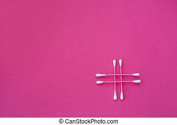 top view on four pink cotton buds with white heads laid out in cross form on a pink background