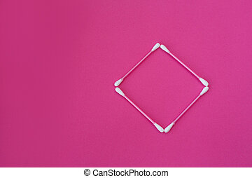 top view on four pink cotton buds with white heads laid out in rhombus form on a pink background