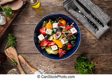 Top view on fresh greek salad in a black bowl
