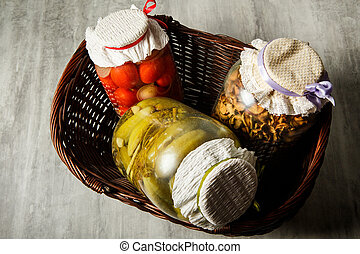 top view on glass jars with homemade canned vegetables lie in basket