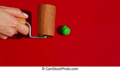 top view on hand puts small piece of bright green homemade marzipan mass and roll it out by special confectionery wooden roller on red surface