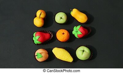 top view on hand takes away fruit shaped marzipan candy from assortment