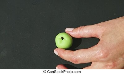 top view on hands take green marzipan apple shape candy and brown paper stand
