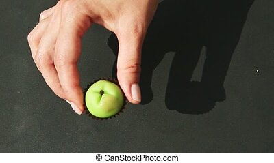 top view on human hand shows small green apple shaped marzipan candy