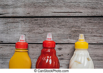 top view on mustard and ketchup with mayo sauces at bottles laying on wooden table, wooden background