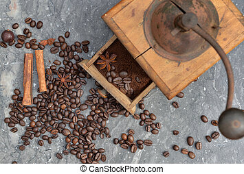 top view on old coffee grinder full of coffee and beans with spices on grey marble