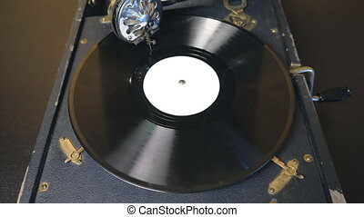 Top view on old playing gramophone. Needle sliding smoothly on black vinyl record spinning at vintage turntable. Retro concept. Slow motion Close up.