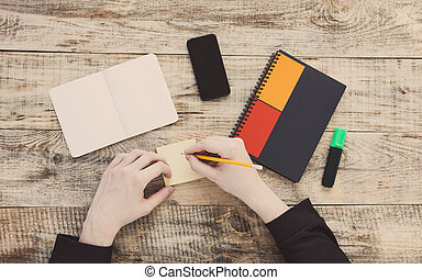 Top view on opened notebook, smartphone, highlighters, sticky note, and other equipment on wooden office desk. Hipster style