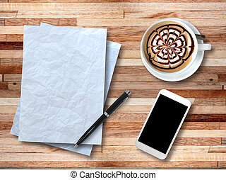 Top view on paper, smartphone, pen and cup of coffee on wooden desk.
