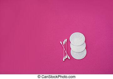 top view on pink cotton buds with white heads and white round cotton disks laid out on a pink background