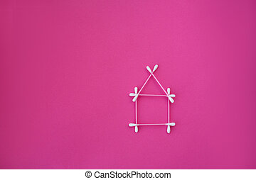 top view on pink cotton buds with white heads laid out in house form on a pink background