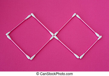 top view on pink cotton buds with white heads laid out in rhombus form on a pink background
