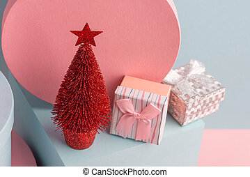 Top view on pink gift boxes and red Christmas tree with star on teal background