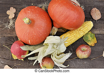 top view on pumpkins, maize and apples arranged on a wooden background