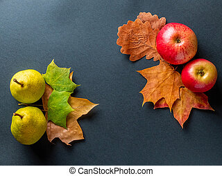 Top view on red apples, yellow pears and colorful autumn leaves on a dark gray background. Top view with space for text.