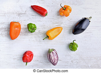top view on small peppers and eggplants on white table