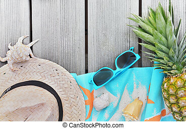 top view on straw hat, beach towel, sunglasses and pineapple on wooden terrace