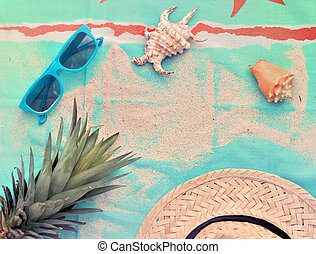 top view on sunglasses, pineapple, straw hat and shells on a beach towel